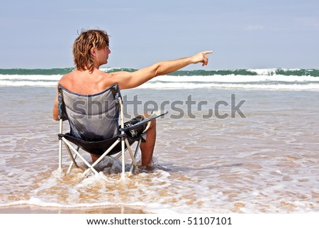 Young guy relaxing at the ocean and pointing to the waves