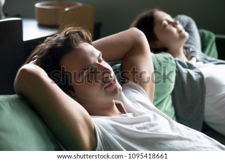 Young guy relaxing on comfortable couch with girlfriend at home, happy man and woman enjoying rest or having nap on sofa, relaxed couple breathing fresh air meditating dozing on daytime together