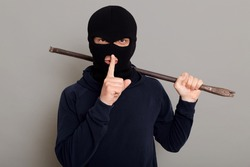 Young guy robber man dressed in a black hoodie with masked face, holds iron crowbar in his hands, shows silence gesture, keeping fore finger near his lips, isolated on gray background