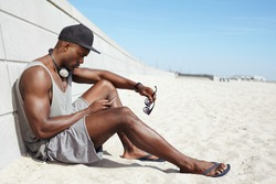 Young guy sending a text message at the beach. African man sitting on beach using mobile phone. Muscular male model outdoors.