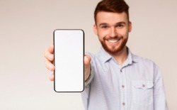 Young guy showing his phone with blank space on camera and smiling, panorama