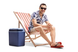 Young guy sitting in a deck chair next to a cooling box and looking at the camera isolated on white background