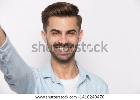 Young guy smiling looking at cam view from web camera isolated on white studio background, millennial positive man using smartphone taking self portrait makes photography modern wireless usage concept #1410240470
