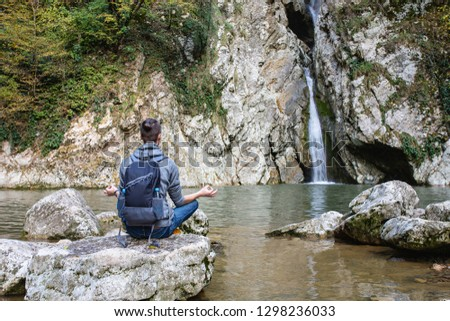 Young guy tourist in casual clothes with backpack sits in picturesque place on stone overlooking waterfall and meditates alone. Concept of self-knowledge of self-improvement and self-identification