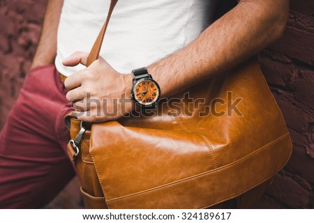 young guy with a beard and mustache  and white T-shirt  posing on the street  vintage man, fashion men, hipster street casual  leather bag and hours against the background of a brick wall