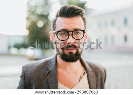 young guy with a beard and mustache with glasses in a suit posing on the street in the sunlight