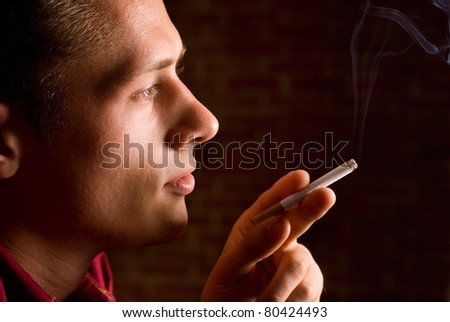 young guy with cigarette on a brick background