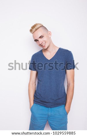young guy with dyed hair stands near an old textured wall. street summer style in clothes: blue shirt and blue shorts. emotional portrait of a student. clean leather and short hair