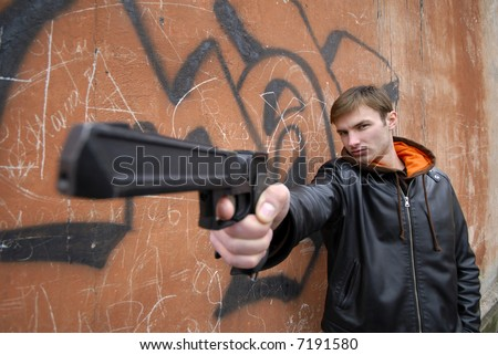 young guy with  pistol in  hand on  background of  wall