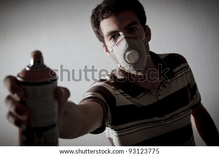 young guy with spray can in backlight