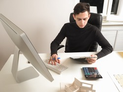 Young guy works as an auditor. Auditor next to the computer. Financial auditor at work. Young guy works in the office. Concept - an employee of a consulting bureau. Auditing services.