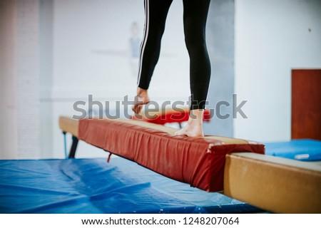 Young gymnast balancing on a balance beam #1248207064