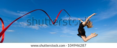 Young gymnast jumping with  ribbon outdoor