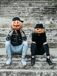 young halloween couple of man in cap and girl or woman in black witch hat in jeans sitting on stony stairs with traditional autumn holiday symbol of orange spooky pumpkin outdoor