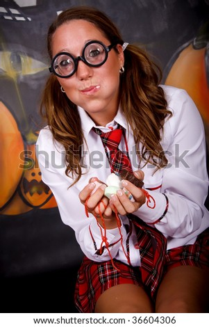 Young Halloween female with English boarding school student outfit gulping sweets.    Studio shot, painted background.