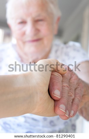 Young hand holding senior lady's hand