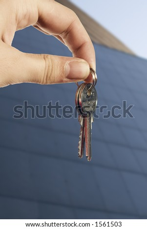 Young hand with keys in front of business office building