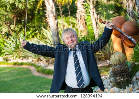 Young handicapped musician raising arms with violin outdoors.