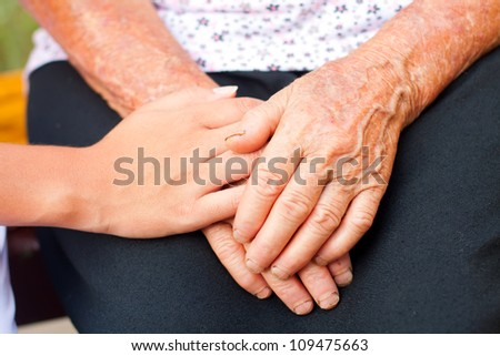 Young hands between elderly ones.