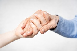 Young hands hold old hands. Help for the elderly concept.