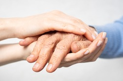 Young hands hold old hands. Support for the elderly concept.