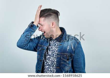 Young handsom man in fashion shirt keeping his hand on head, like decision has come isolated on gray background. People sincere emotions concept Mock up
