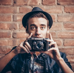 Young, handsome, a little surprised and interested guy in a hat with a vintage camera. Against the background of a brown brick wall.  Photographer. Vintage stylized photo