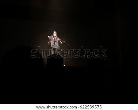Young handsome actor reads a monologue on stage