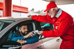 Young handsome adult man together with senior worker standing on gas station and fueling car and paying with credit card.