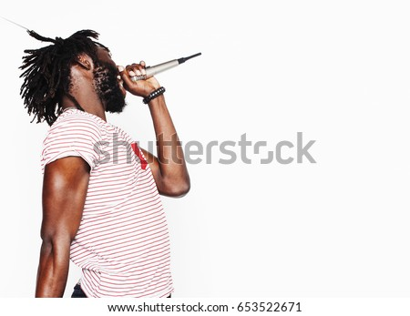 young handsome african american boy singing emotional with microphone isolated on white background, in motion gesturing smiling, lifestyle people concept  ストックフォト ©