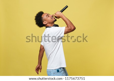 Young handsome African American Male Singer Performing with Microphone. Isolated over yellow gold background. ストックフォト ©