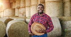 Young handsome African American man farmer standing and smiling in barn with hay barn. Portrait of happy cheerful male shepherd taking off hat and doing greeting gesture in stable. Outdoor.