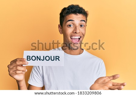 Young handsome african american man holding bonjour french greeting word celebrating achievement with happy smile and winner expression with raised hand  Photo stock ©