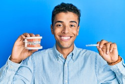 Young handsome african american man holding invisible aligner orthodontic and braces smiling with a happy and cool smile on face. showing teeth.