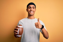 Young handsome african american man holding rugby ball over isolated yellow background happy with big smile doing ok sign, thumb up with fingers, excellent sign