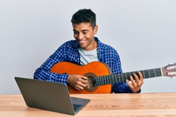Young handsome african american man learning classical guitar from online tutorial looking positive and happy standing and smiling with a confident smile showing teeth