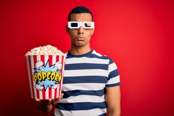 Young handsome african american man watching movie using 3d glasses eating popcorns depressed and worry for distress, crying angry and afraid. Sad expression.