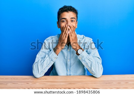 Young handsome african american man wearing casual clothes sitting on the table laughing and embarrassed giggle covering mouth with hands, gossip and scandal concept  ストックフォト ©