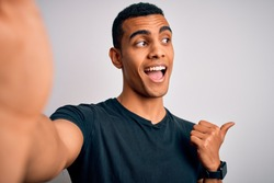 Young handsome african american man wearing casual t-shirt making selfie by camera pointing and showing with thumb up to the side with happy face smiling