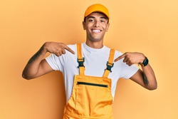 Young handsome african american man wearing handyman uniform over yellow background looking confident with smile on face, pointing oneself with fingers proud and happy.