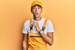 Young handsome african american man wearing handyman uniform over yellow background thinking concentrated about doubt with finger on chin and looking up wondering