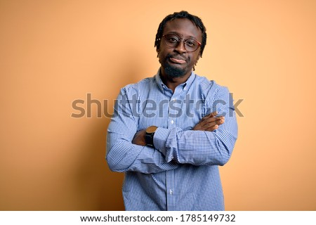 Young handsome african american man wearing shirt and glasses over yellow background skeptic and nervous, disapproving expression on face with crossed arms. Negative person. Сток-фото ©