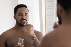 Young handsome african ethnicity 30s bare man looking in mirror, taking medical pills or daily dose of vitamins, drinking glass of fresh pure water, improving immunity system, feeling healthy indoors.