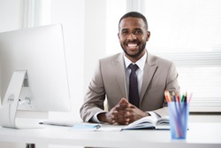 Young handsome africanamerican businessman working alone in the office
