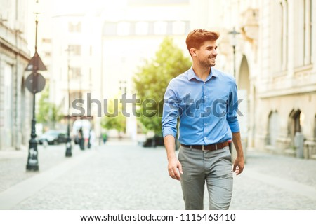 young handsome and confident guy in smart casual outfit, office day, standing outside on the street and looking to side #1115463410