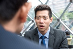 Young handsome Asian Chinese businessman talking to his partner with eye contact at office lounge