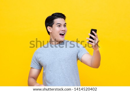 Young handsome Asian man being surprised after reading message from smarrtphone studio short isolated on bright yellow background