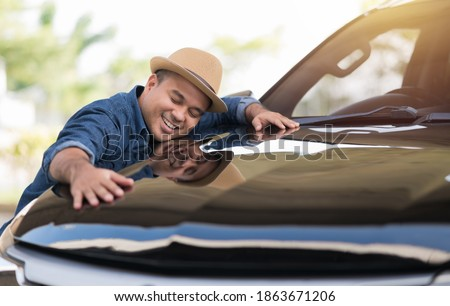 Young handsome asian man getting the new car. He hugged his car and was very happy. Buy or rent car concept.