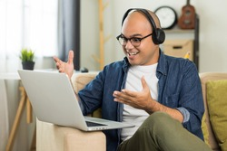 Young handsome asian man meeting and conferencing online keep social distancing talking with his business team online or study online course. He wearing headset.