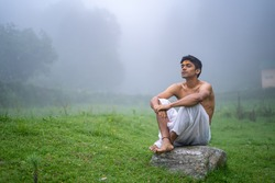Young handsome asian model sitting in the mountains wearing a dhoti in the morning time.